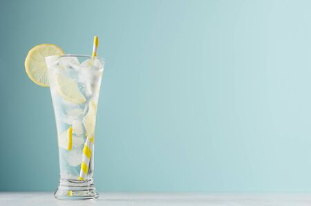 Homemade diet transparent lemonade with lemon, ice cubes, soda, yellow striped straw in misted glass on white wood table, pastel green color background.