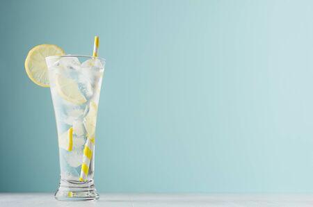 Limonade transparente diététique maison au citron, glaçons, soda, paille rayée jaune en verre embué sur table en bois blanc, fond de couleur vert pastel. Banque d'images