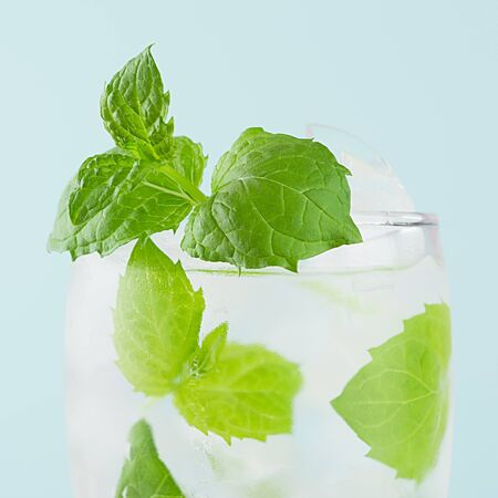 Refreshing summer mint water with green leaf, ice cubes, tonic in light soft pastel blue color background, closeup, top, half, edge, square.
