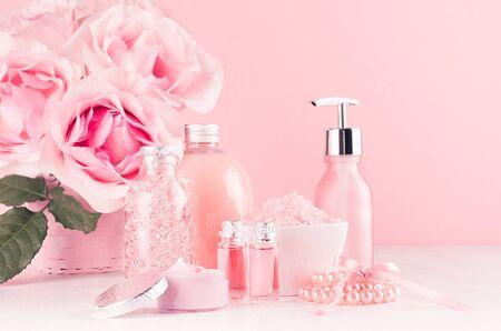 Verschillende huidverzorgingsproducten met romantisch rozenboeket op meisjesachtige elegante roze pastelachtergrond met kopieerruimte. Stockfoto