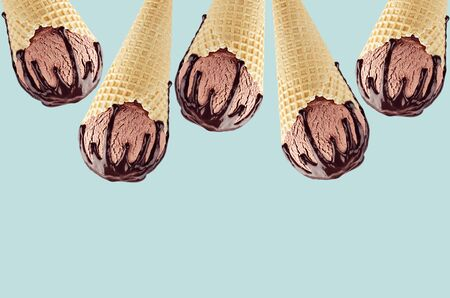 Chocolate ice cream in crisp waffle cones with sweet brown sauce as decorative frame on  green background.