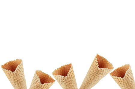 Summer food decorative border of empty waffle ice cream cones isolated on white background, copy space.