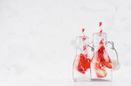 Fresh strawberry lemonades with sliced berry, soda water, straw in transparent yoke bottles on soft light white wood table, copy space.