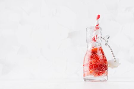 Fresh strawberry lemonade with sliced berry, soda water, straw in transparent yoke bottle on soft light white wood table, copy space.