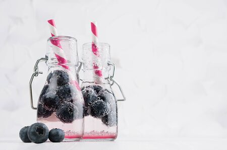 Natural organic pink cocktails with blueberry, carbonated water and striped straw in yoke bottles on bright white wood board and wall, copy space. Stock Photo