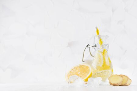 Refreshing cold fruit drink with citrus lemon, bright bubbles, ice, ginger and straw in transparent yoke bottle in elegant white interior on wood table, copy space. Фото со стока