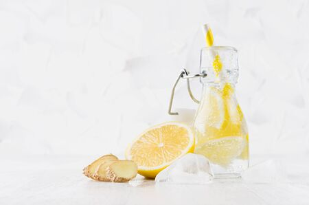 Cold fresh fruit citrus beverage of yellow lemon with soda water, bubbles, ginger, ice, funny striped straw on simple soft bright white background, copy space.