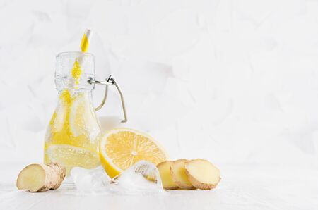 Natural organic cocktail with lemon, carbonated water, slices, ice cubes, ginger and  striped straw in yoke bottle on bright white wood board and wall.