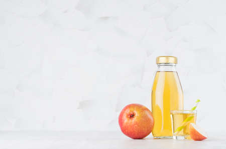 Organic yellow transperent pear juice in glass bottle mock up with straw, wine glass, fruit slice on white wood table in light interior, template for packaging, advertising, design, branding product.