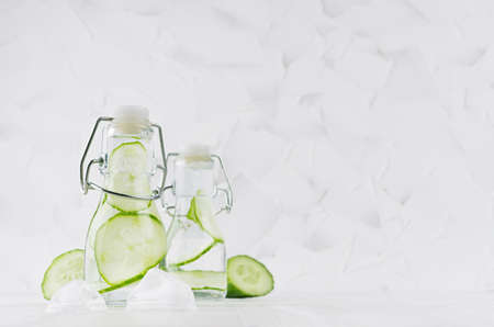 Joy bright fresh summer drinks with green cucumber, ice cubes, soda water in two elegant yoke bottles on soft light white wood table, copy space.