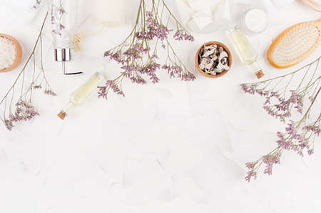 Elegant beige natural cosmetic products and accessories with lavender twigs for body and skin care on soft light white background, top view, copy space. Banco de Imagens