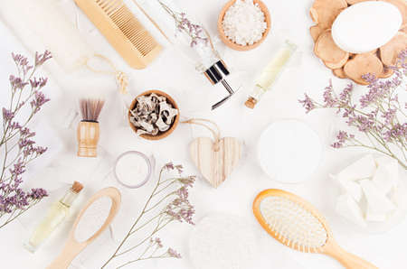 Elegant light natural bath accessories and beauty products for hygiene and body care with lavender twigs, heart on white background, flat lay.