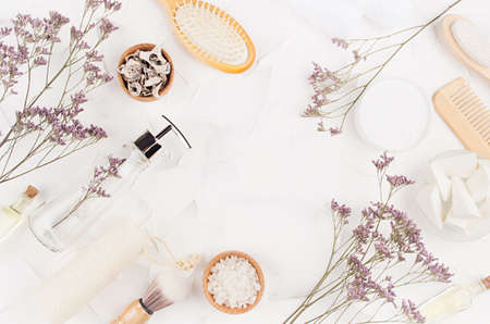 Natural beige cosmetics accessories and product for bathroom with dry lavender twigs on white background, copy space, border, top view, frame. Banco de Imagens