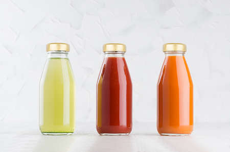 Tomato, carrot, green vegetable juices set in glass bottles with cap mock up in row on white wood table in light interior, template for packaging, advertising, design product, branding.