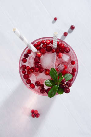 Sour pink cocktail of lingonberry with red berry, ice cubes and straws on white wood board, closeup, top view, vertical.