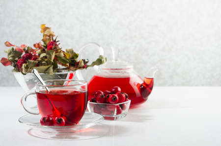 Morning autumn teatime with red herbal tea in transparent tea pot, cup with hawthorn, rosehip berry, dried leaves in sun beam in soft light white interior.