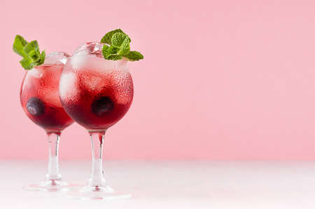 Fresh red berry cocktail with ice cubes, blueberry, green mint in elegant misted goblets on soft light pink color background.