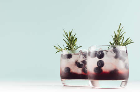 Sweet alcoholic cocktails with ice cubes, blueberry, rosemary in two glasses in soft light mint color bar interior, copy space.