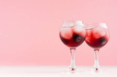Modern refreshing alcohol red drinks in wineglasses with ice cubes, blueberry on white wood board and pastel pink background, copy space.