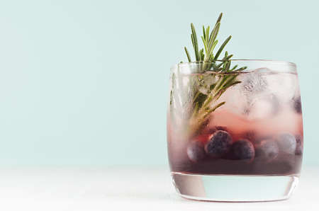 Summer fresh blueberry cocktail in glass with berry, ice cubes, rosemary on white wood table and pastel mint color wall, copy space.
