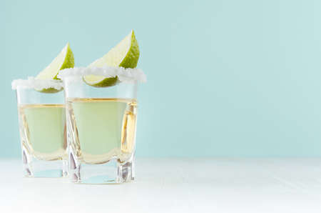Golden mexican alcohol drink tequila with slice lime, salt on edge in shot drink on green color background, white wood board.