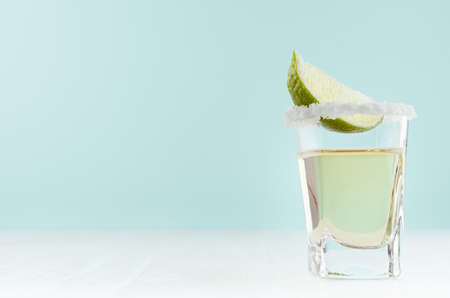 Tequila cocktail with fresh piece lime, rim of salt in shot glass on white wood table and blue color wall, copy space.