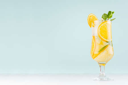 Oranges detox water with sliced orange, ice cubes, green mint in misted wineglass on pastel blue background, white wood board.