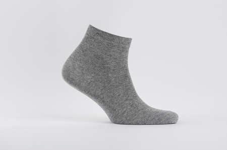 Gray black cotton short sock on invisible foot as mock up for advertising, branding, design. Side view, sportwear template on white background. Zdjęcie Seryjne