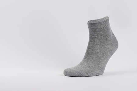 Gray black cotton sock medium size on invisible foot as mock up for advertising, branding, design. Front view with copy space, template on white background.