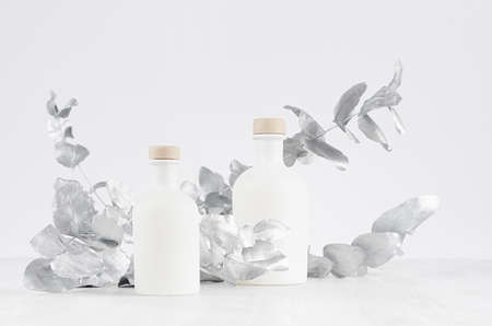 Blank cosmetic glass white bottles with beige bungs decorated silver leaves on light white wood table as mock up for advertising, branding identity, design.
