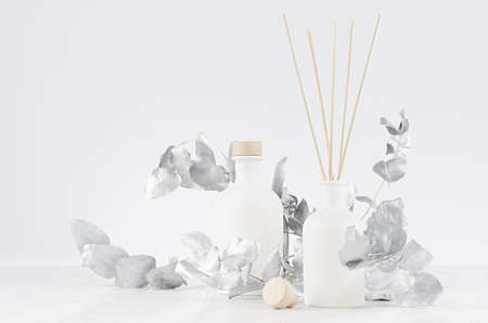 Blank aromatic glass white bottles with beige bungs, sticks decorated silver leaves on light white wood table as modern home decoration.