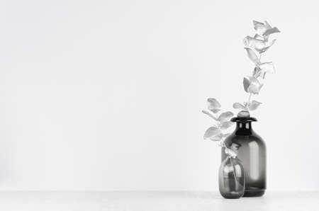 Modern exquisite decoration for home interior - black glass vase with silver leaves on white wood background.