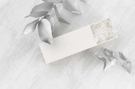 Exquisite white blank open rectangle gift box with paper filler mock up on wood board silver leaves top view for design, branding identity, presentation.