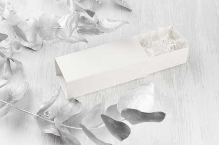 Stylish white blank open rectangle gift box with paper filler mock up on wood board silver leaves side view for design, branding identity, presentation.