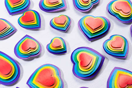 Lgbt Valentines day background - rainbow handmade valentines hearts on white wood board, pattern, top view.
