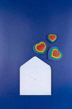 Lgbt Valentines day background - open white blank envelope as love note with flying rainbow hearts on dark blue backdrop, top view.