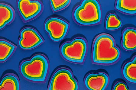 Valentine day background with rainbow hearts on dark blue paper as pattern, top view. Zdjęcie Seryjne