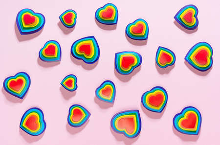 Lgbt Valentines day background - rainbow hearts as abstract pattern on pastel pink backdrop, top view.