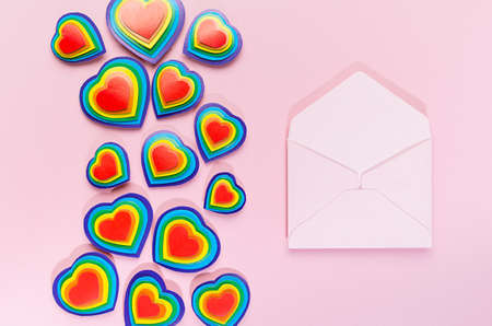 Valentine day background with open blank envelope as love note and rainbow hearts on pastel pink paper, top view. Zdjęcie Seryjne