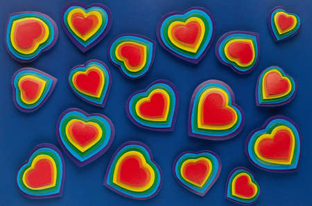 Lgbt Valentines day background - rainbow hearts as abstract pattern on dark blue backdrop, top view.