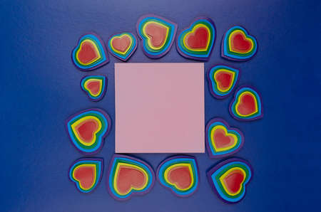 Handmade rainbow hearts with blank square paper pink card for text on dark blue background, valentine day.