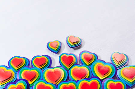 Lgbt Valentines day background - rainbow handmade valentines hearts on white wood board, border, top view.