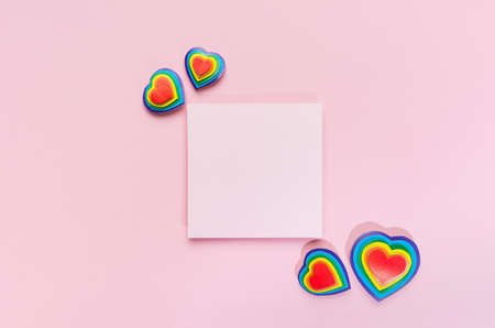 Colorful lgbt Valentine day background - multicolored hearts with blank square paper for text on pastel pink backdrop, top view, mockup.
