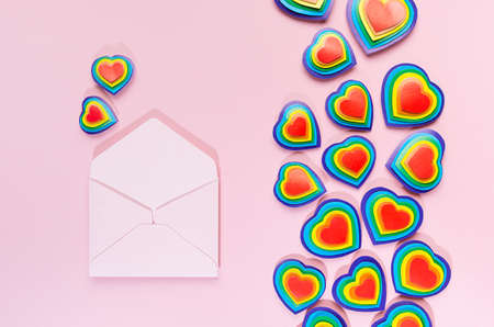 Rainbow hearts on pastel pink background with open blank pink envelope as love note, top view. Zdjęcie Seryjne