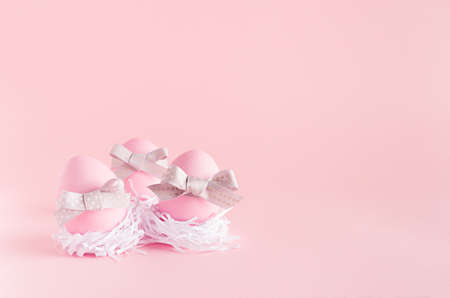 Festive easter background - pink easter eggs with silver bows in white nest on pastel pink backdrop.