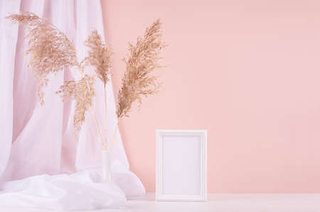 Delicate home decor with blank wooden poster frame, silk curtain and fluffy reeds in vase on white wooden table and pastel pink wall. Mock up for portfolio. 免版税图像