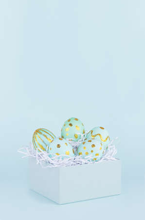 Simple and minimal easter background - easter eggs with golden design in gift box on blue color, vertical.