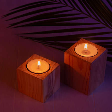 Night tropical atmosphere for vacation and relaxation with burning candles and pal leaf in purple orange sunset light, square, top view.