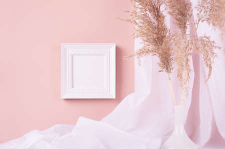 Elegant home decoration - square blank photo frame hanging on pink wall, curtain, beige fluffy reeds in vase. Contemporary simple life style. 免版税图像