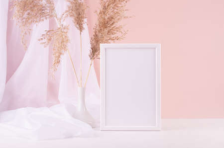 Calm home decor with blank photo frame for text, silk curtain, fluffy reeds bouquet on white wood table, pink wall. Template for display and portfolio.